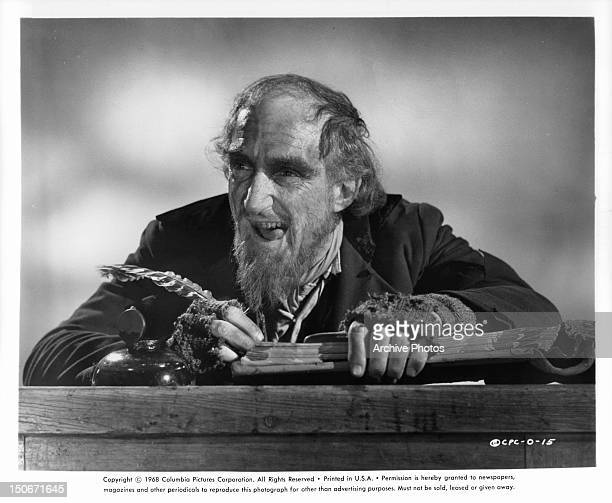 Ron Moody, as Fagin, writing in book in publicity portrait for the film 'Oliver!', 1968.