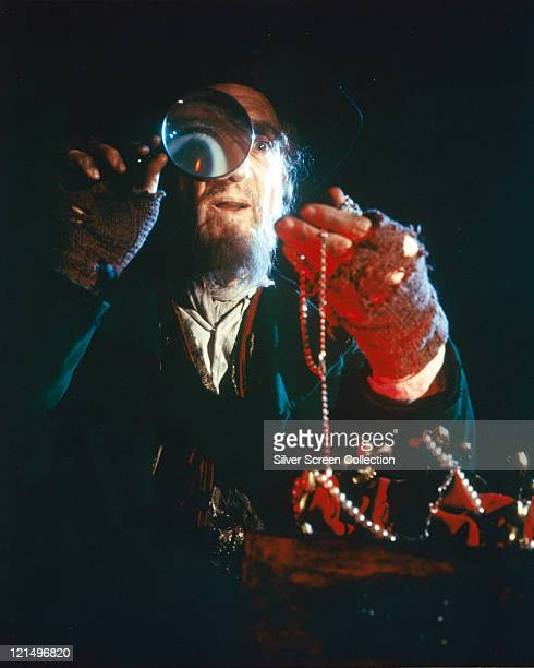 Ron Moody, British actor, peering through a magnifying glass as he examines jewelley in a publicity still issued for the film, 'Oliver!', 1968. The...