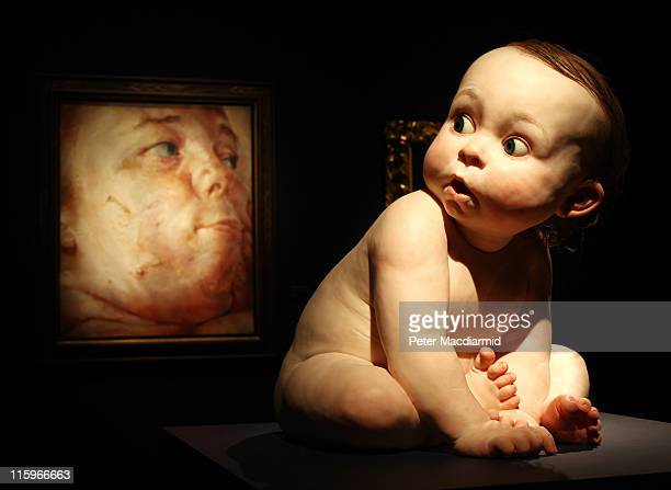 Ron Mueck's 'Big Baby' sculpture appears to look round at Jenny Saville's painting 'Interfacing' at the Masterpieces Exhibition at Christie's on June...
