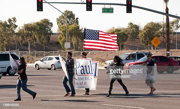 Ron Paul campaigners carry signs and a flag across a busy street February 25 2012 in Peoria Arizona The Arizona and Michigan primaries are scheduled...