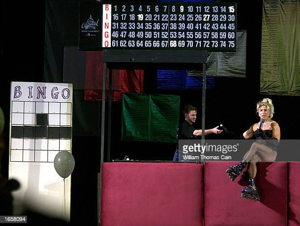 Ron Powers hands a bingo ball to Stella Cumming as she calls out numbers during Gay Bingo November 23 2002 in Philadelphia Pennsylvania Since it...