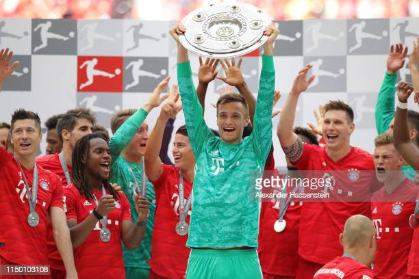 Ron Thorben Hoffmann of Bayern Munich lifts the trophy following the Bundesliga match between FC Bayern Muenchen and Eintracht Frankfurt at Allianz...