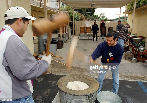 Ron Tokunaga and Curt Yasuhara pound rice in a concrete bowl as they participate in making Japanese rice cakes called mochi 14 December at the...