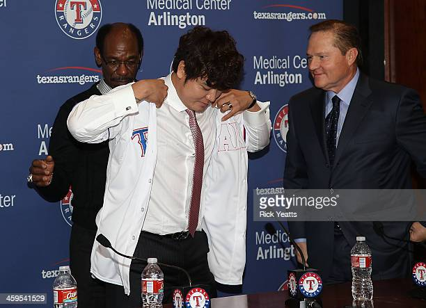 Ron Washington assists Shin-Soo Choo with his new jersey as Choo's agent Scott Boras looks on during the press conference introducing Choo at Rangers...