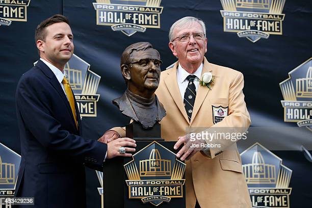 Ron Wolf and his son Eliot pose with Wolf's bust during the NFL Hall of Fame induction ceremony at Tom Benson Hall of Fame Stadium on August 8 2015...
