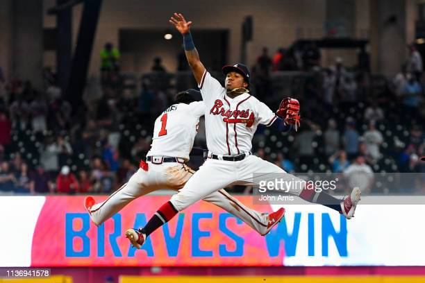 Ronald Acuna Jr. #13 and Ozzie Albies of the Atlanta Braves celebrate an 11-7 win over the New York Mets at SunTrust Park on April 13, 2019 in...