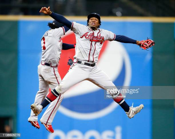 Ronald Acuna Jr. #13 and Ozzie Albies of the Atlanta Braves celebrate an 11-5 victory over the Cleveland Indians at Progressive Field on April 21,...