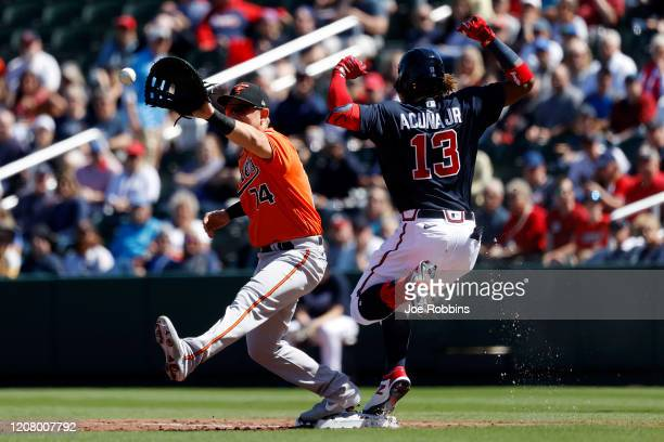 Ronald Acuna Jr #13 of the Atlanta Braves beats the throw at first base to Pat Valaika of the Baltimore Orioles in the first inning of a Grapefruit...