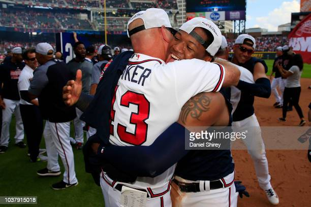 Ronald Acuna Jr #13 of the Atlanta Braves celebrates with manager Brian Snitker after clinching the NL East Division against the Philadelphia...