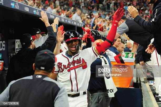Ronald Acuna Jr #13 of the Atlanta Braves celebrates with teammates in the dugout after hitting a grand slam home run in the second inning against...