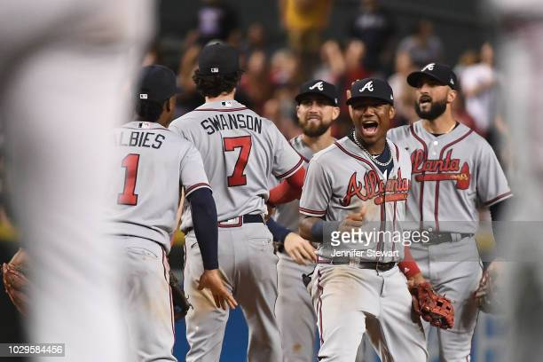 Ronald Acuna Jr #13 of the Atlanta Braves celebrates with teammates after defeating the Arizona Diamondbacks in the tenth inning of the MLB game at...