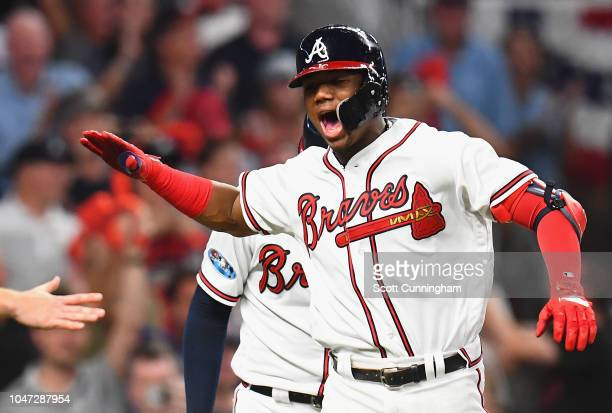 Ronald Acuna Jr #13 of the Atlanta Braves celebrates with teammates after hitting a grand slam home run in the second inning against the Los Angeles...