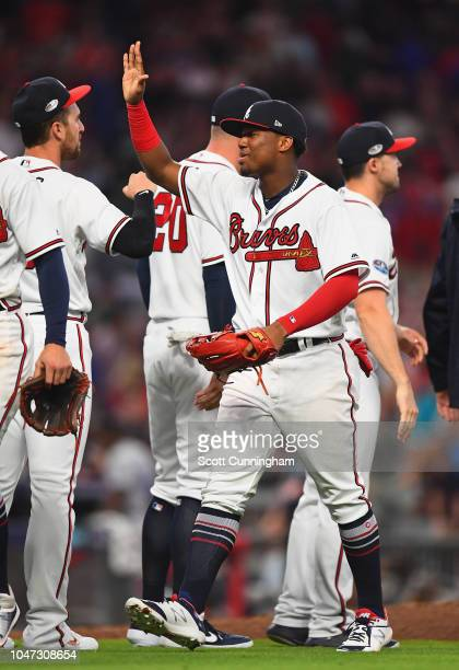 Ronald Acuna Jr. #13 of the Atlanta Braves celebrates with teammates after defeating the Los Angeles Dodgers 6-5 in Game Three of the National League...