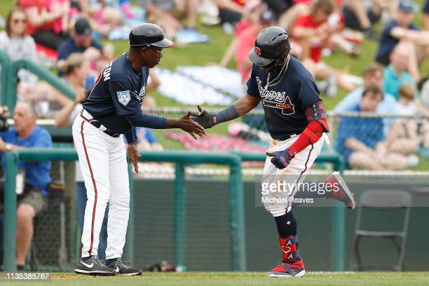 Ronald Acuna Jr #13 of the Atlanta Braves celebrates with third base coach Ron Washington after hitting a solo home run in the fourth inning against...