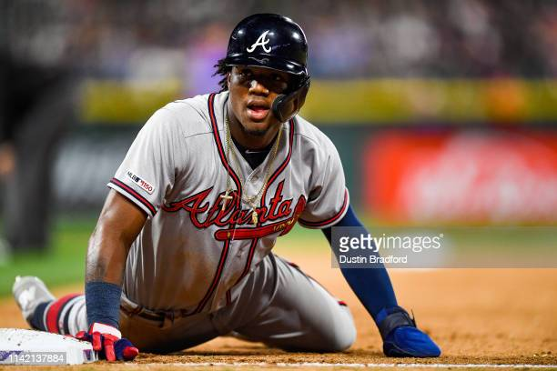 Ronald Acuna Jr. #13 of the Atlanta Braves dives back to first base to avoid a pickoff in the fifth inning of a game against the Colorado Rockies at...