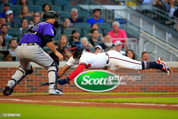 Ronald Acuna Jr #13 of the Atlanta Braves dives into home before the tag by Chris Iannetta of the Colorado Rockies to score a run during the first...