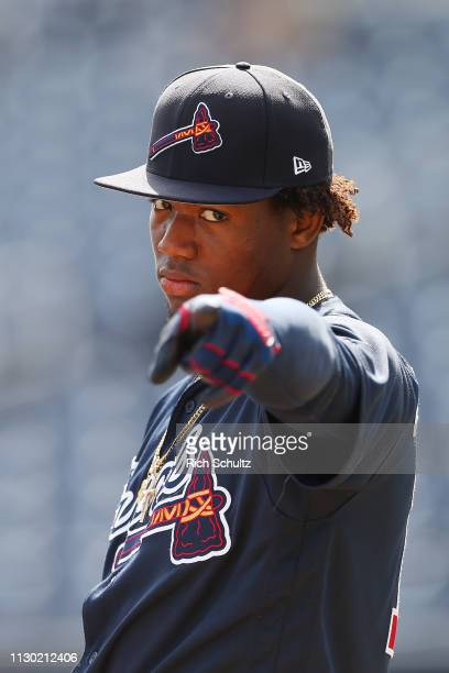 Ronald Acuna Jr #13 of the Atlanta Braves gestures during batting practice before a spring training baseball game against the Washington Nationals at...