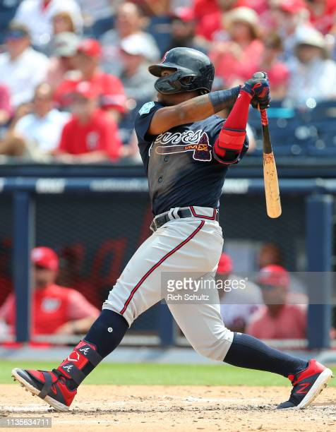 Ronald Acuna Jr #13 of the Atlanta Braves hits an RBI triple against the Washington Nationals during the third inning of a spring training baseball...