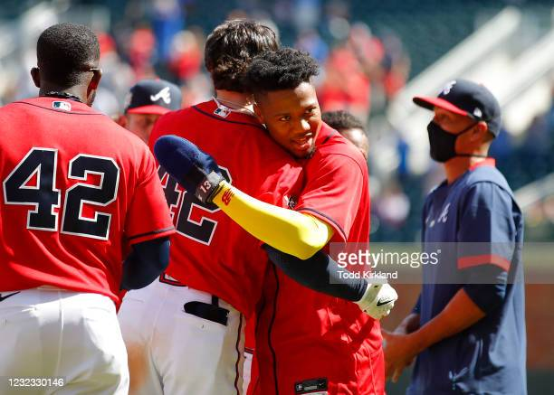 Ronald Acuna Jr. #13 of the Atlanta Braves hugs Dansby Swanson at the conclusion of an MLB game against the Miami Marlins at Truist Park on April 15,...