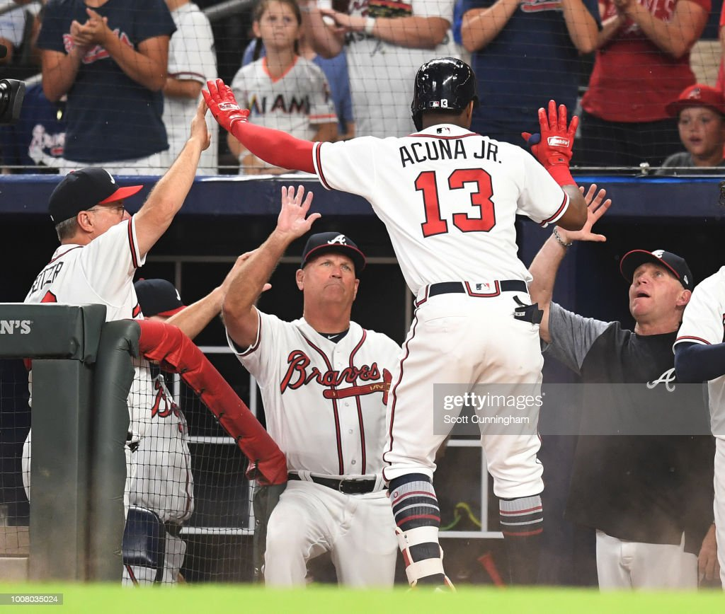 Ronald Acuna, Jr. #13 of the Atlanta Braves is congratulated by teammates after hitting a fifth inning solo home run against the Miami Marlins at SunTrust Park on July 30, 2018 in Atlanta, Georgia.