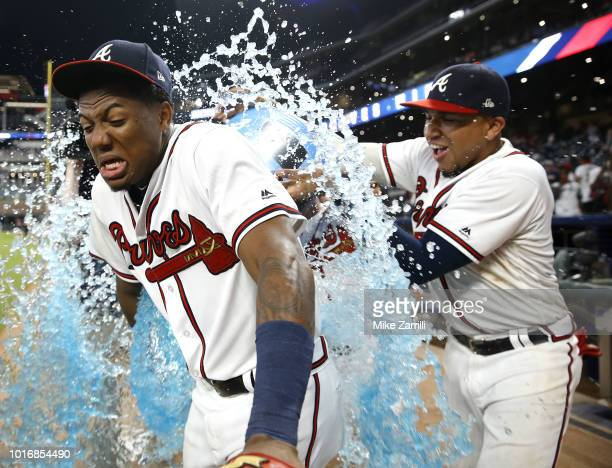 Ronald Acuna Jr #13 of the Atlanta Braves is doused with Powerade by teammates Charlie Culberson and Johan Camargo after the game against the Miami...