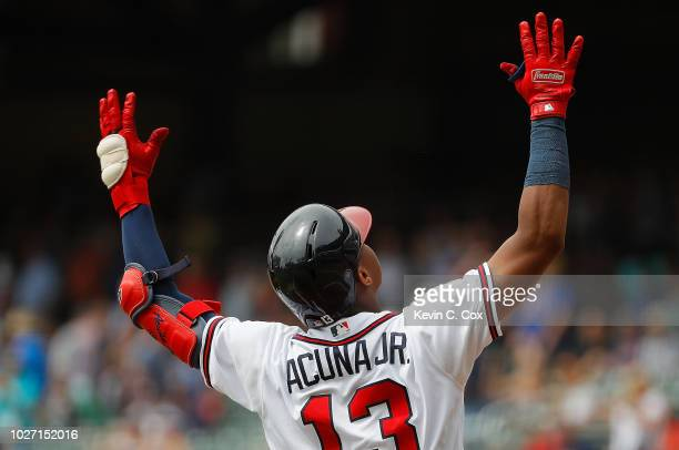 Ronald Acuna Jr #13 of the Atlanta Braves reacts after hitting a solo homer to lead off the first inning against the Boston Red Sox at SunTrust Park...