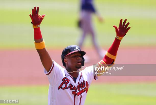Ronald Acuna Jr. #13 of the Atlanta Braves reacts after hitting a solo homer to lead off the first inning against the Toronto Blue Jays at Truist...