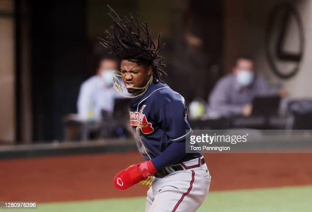 Ronald Acuna Jr. #13 of the Atlanta Braves reacts after scoring a run against the Los Angeles Dodgers during the first inning in Game Seven of the...