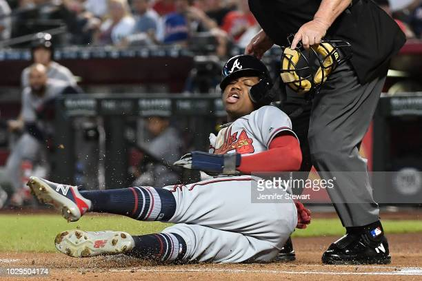 Ronald Acuna Jr #13 of the Atlanta Braves safely scores while sliding in to umpire Joe West in the first inning of the MLB game against the Arizona...