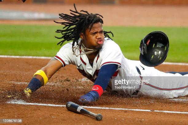 Ronald Acuna Jr. #13 of the Atlanta Braves slides into home to score on a double in the first inning of an MLB game against the Miami Marlins at...