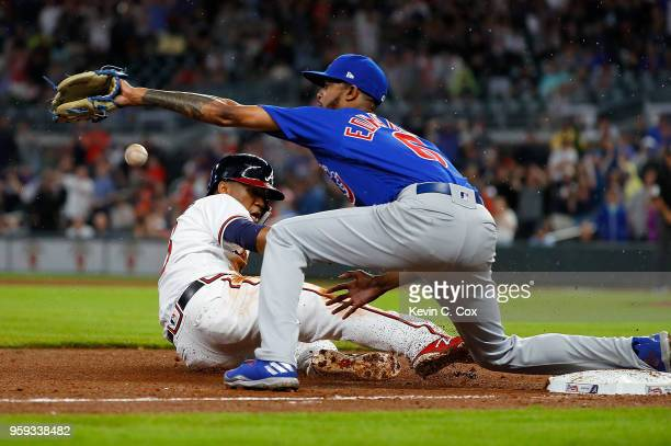 Ronald Acuna Jr #13 of the Atlanta Braves slides safely into third base against Carl Edwards Jr #6 of the Chicago Cubs on a single hit by Freddie...
