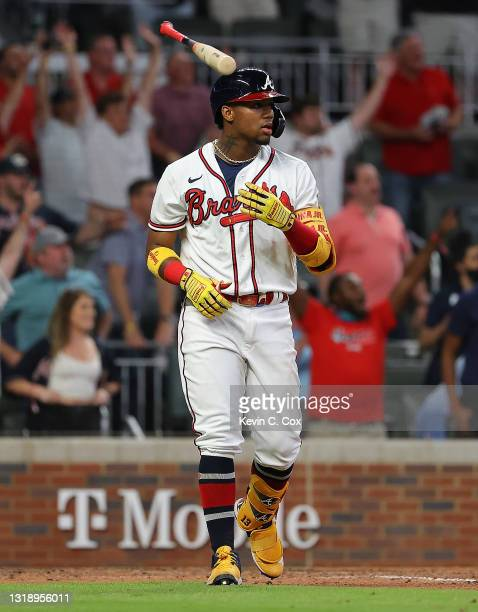 Ronald Acuna Jr. #13 of the Atlanta Braves tosses his bat after hitting a walk-off homer in the ninth inning against the New York Mets at Truist Park...
