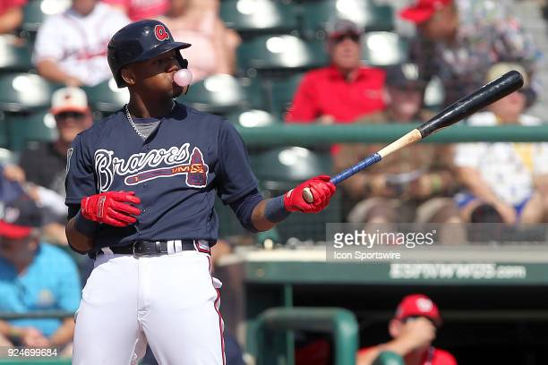 Ronald Acuna Jr of the Braves blows a bubble as he stands in a batter's box during the spring training game between the Washington Nationals and the...