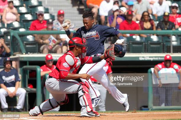 Ronald Acuna Jr of the Braves hustles home to score a run a head of the tag by Pedro Severino of the Nationals during the spring training game...