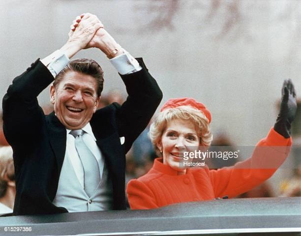 Ronald and Nancy Reagan waving and clasping hands in victory at Reagan's first inauguration, January 20, 1981.