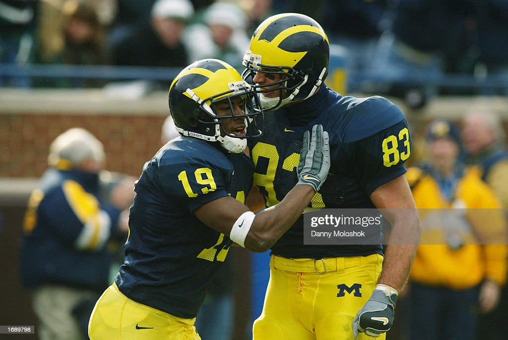 Ronald Bellamy #19 and Bennie Joppru #83 of the Michigan Wolverines celebrate against the Michigan State Spartans during the game on November 2, 2002 at Michigan Stadium in Ann Arbor, Michigan. Michigan won 49-3.