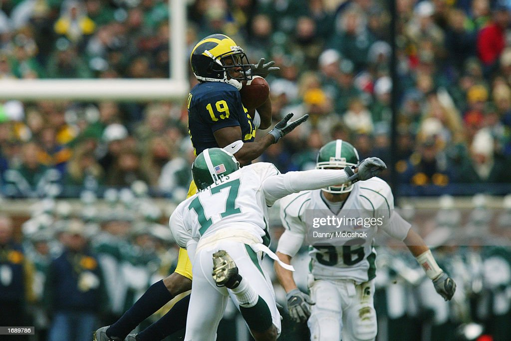 Ronald Bellamy #19 of the Michigan Wolverines makes a catch as Roderick Maples #17 and Eric Smith #36 of the Michigan State Spartans go for the tackle during the game on November 2, 2002 at Michigan Stadium in Ann Arbor, Michigan. Michigan won 49-3.