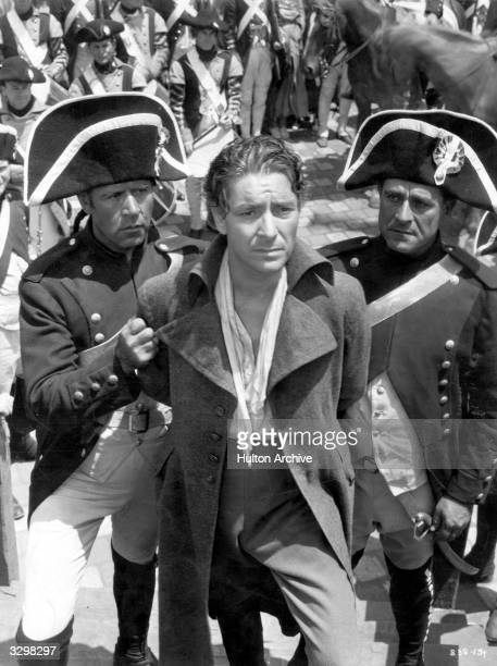 Ronald Colman the British romantic actor who left for Hollywood in 1920 is being led to the guillotine by two soldiers in a scene from 'A Tale of Two...