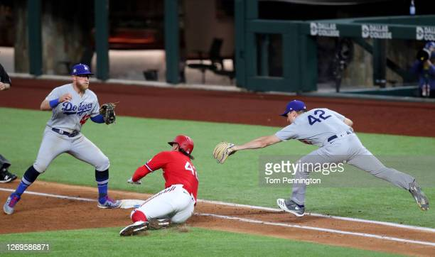 Ronald Guzman of the Texas Rangers avoids the tag and slides safe into first base against starting pitcher Ross Stripling of the Los Angeles Dodgers...