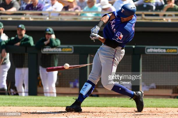 Ronald Guzman of the Texas Rangers breaks his bat while singling against the Oakland Athletics during the spring training game at HoHoKam Stadium on...