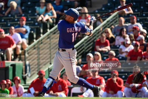 Ronald Guzman of the Texas Rangers hits a solo home run in the spring training game against the Los Angeles Angels at Tempe Diablo Stadium on...