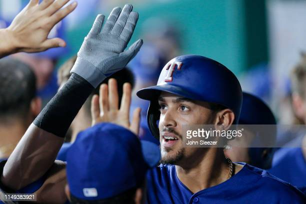 Ronald Guzman of the Texas Rangers is congratulated in the dugout after hitting a two run home run in the sixth inning during the game against the...