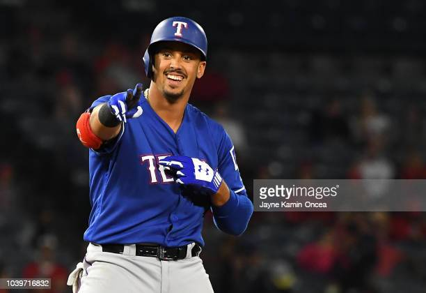 Ronald Guzman of the Texas Rangers smiles at the dugout after hitting a double in the ninth inning against the Los Angeles Angels of Anaheim at Angel...
