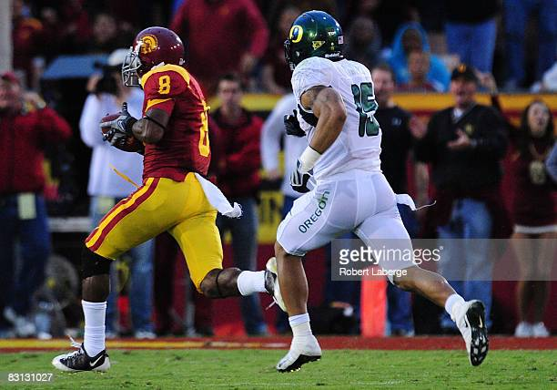 Ronald Johnson of the USC Trojans runs in for a touchdown after making a catch as Patrick Chung of the Oregon Ducks tries to catch him during the...