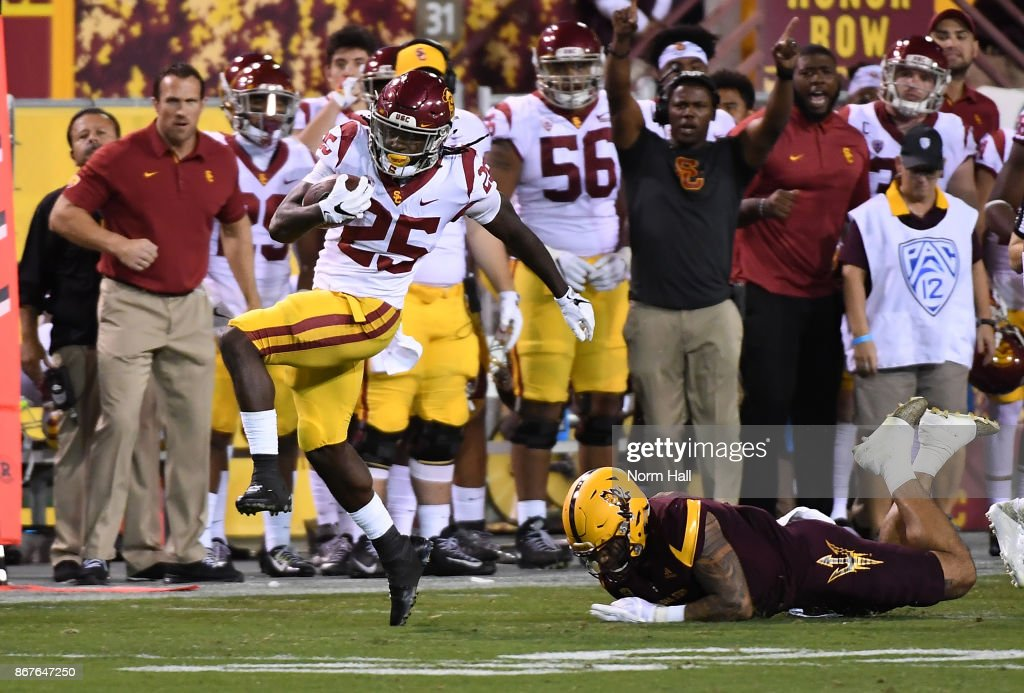Ronald Jones II #25 of Southern California scores a 67 yard touchdown after breaking a tackle by Eric Fields #6 of Arizona State during the first half at Sun Devil Stadium on October 28, 2017 in Tempe, Arizona.