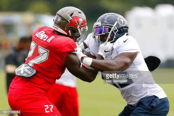 Ronald Jones II of the Bucs blocks Daren Bates of the Titans during the joint training camp work out between the Tampa Bay Buccaneers and the...