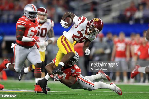 Ronald Jones II of the USC Trojans runs the ball against Jordan Fuller of the Ohio State Buckeyes in the third quarter during the Goodyear Cotton...