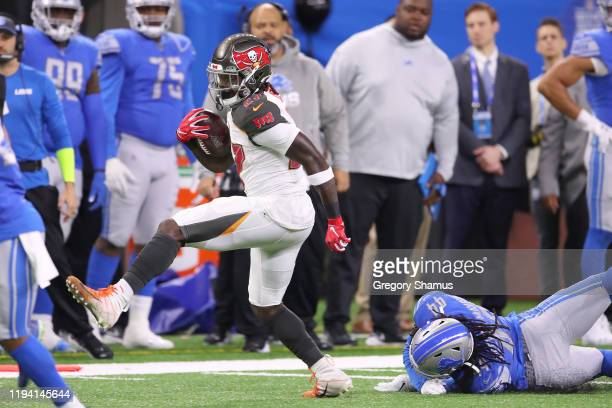 Ronald Jones of the Tampa Bay Buccaneers breaks a tackle by Jalen Reeves-Maybin of the Detroit Lions during a first half run at Ford Field on...