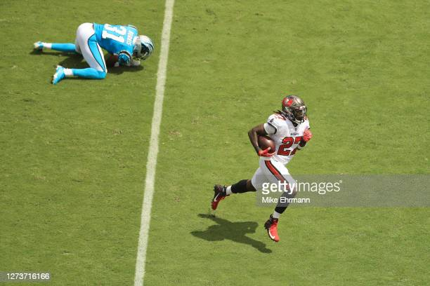 Ronald Jones of the Tampa Bay Buccaneers runs on his way to scoring a first quarter touchdown after stiff arming Juston Burris of the Carolina...