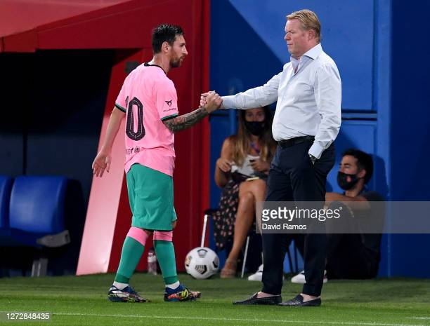 Ronald Koeman, Head Coach of FC Barcelona greets Lionel Messi of FC Barcelona as Lionel Messi is substituted off during the pre-season friendly match...